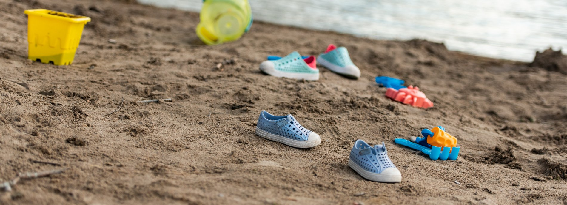 toys and shoes on sandy beach