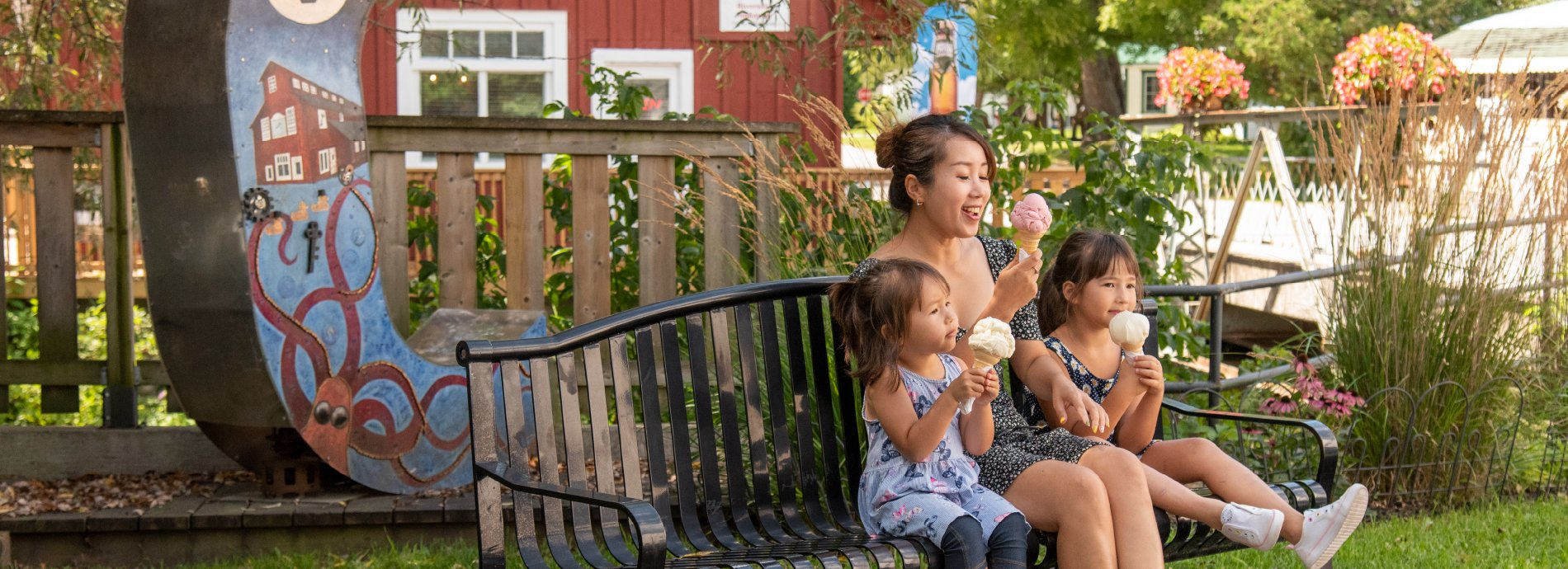 family sitting on a bench eating ice cream